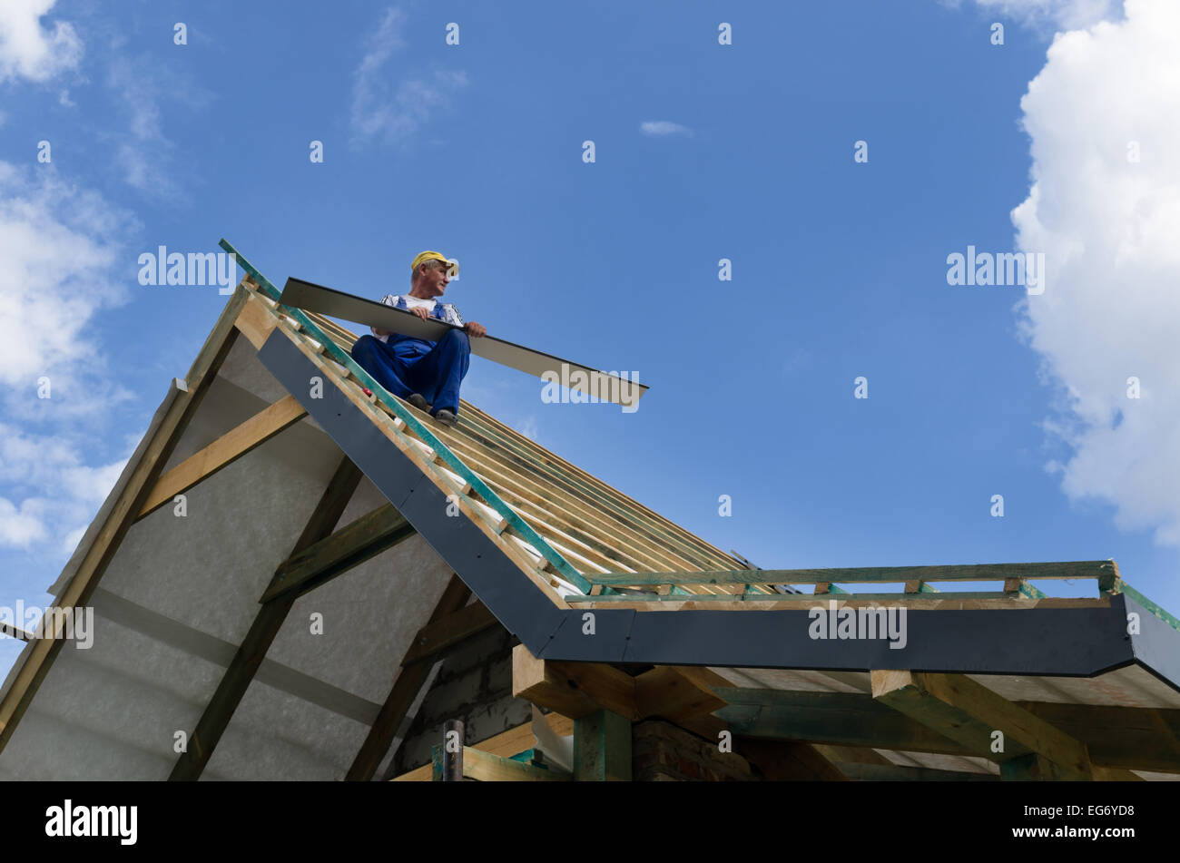 A worker standing on the scaffolding and finishing a roof Stock Photo