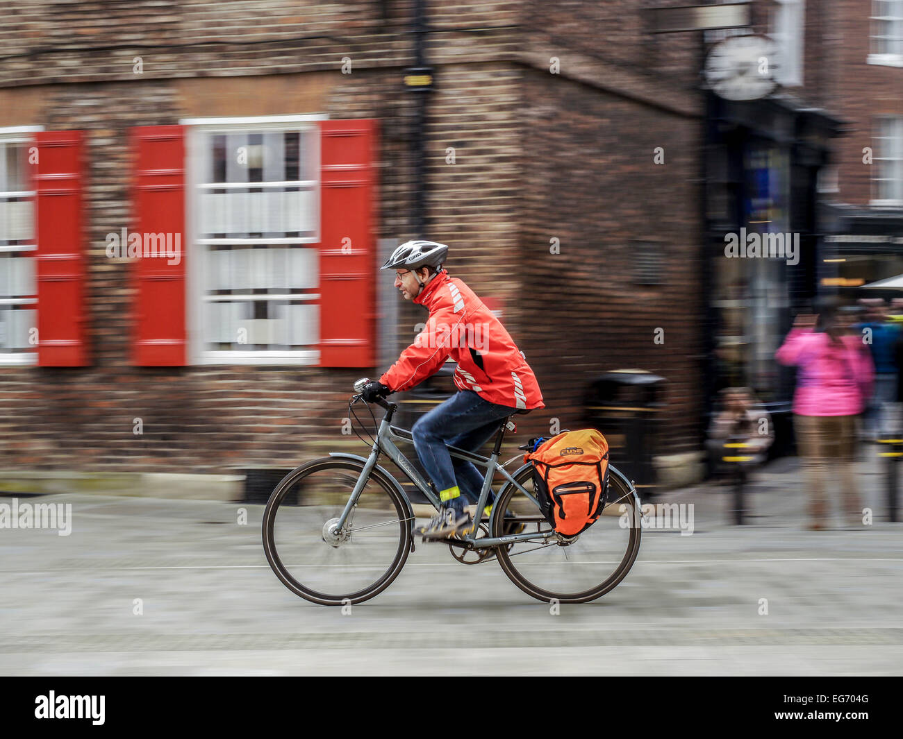 Man in orange jacket a commuter commuting riding grey gray bike cycle bicycle with motion blur of background. - Stock Image