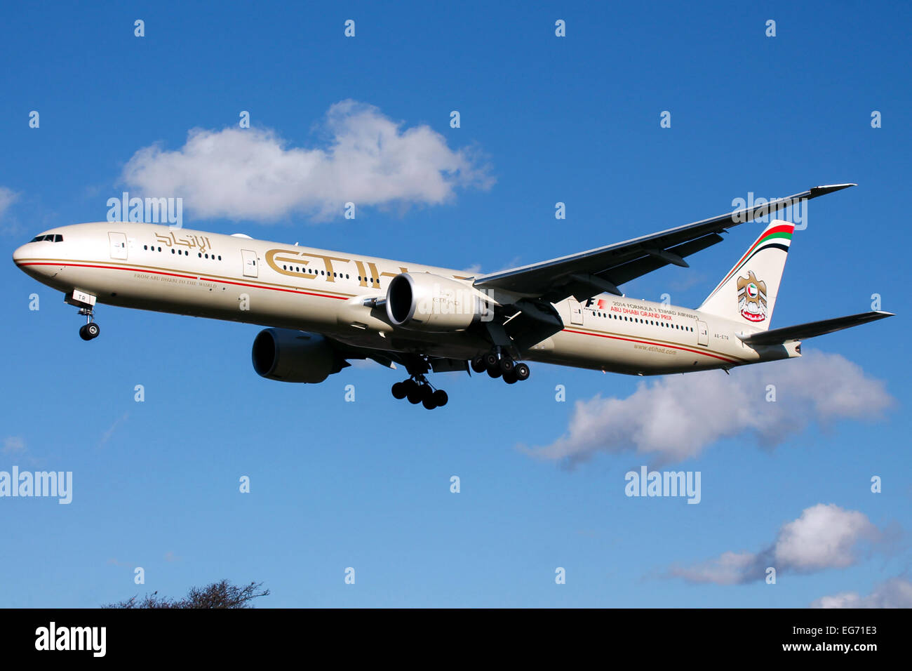 Etihad Airways Boeing 777-300 approaches runway 27L at London Heathrow airport. - Stock Image