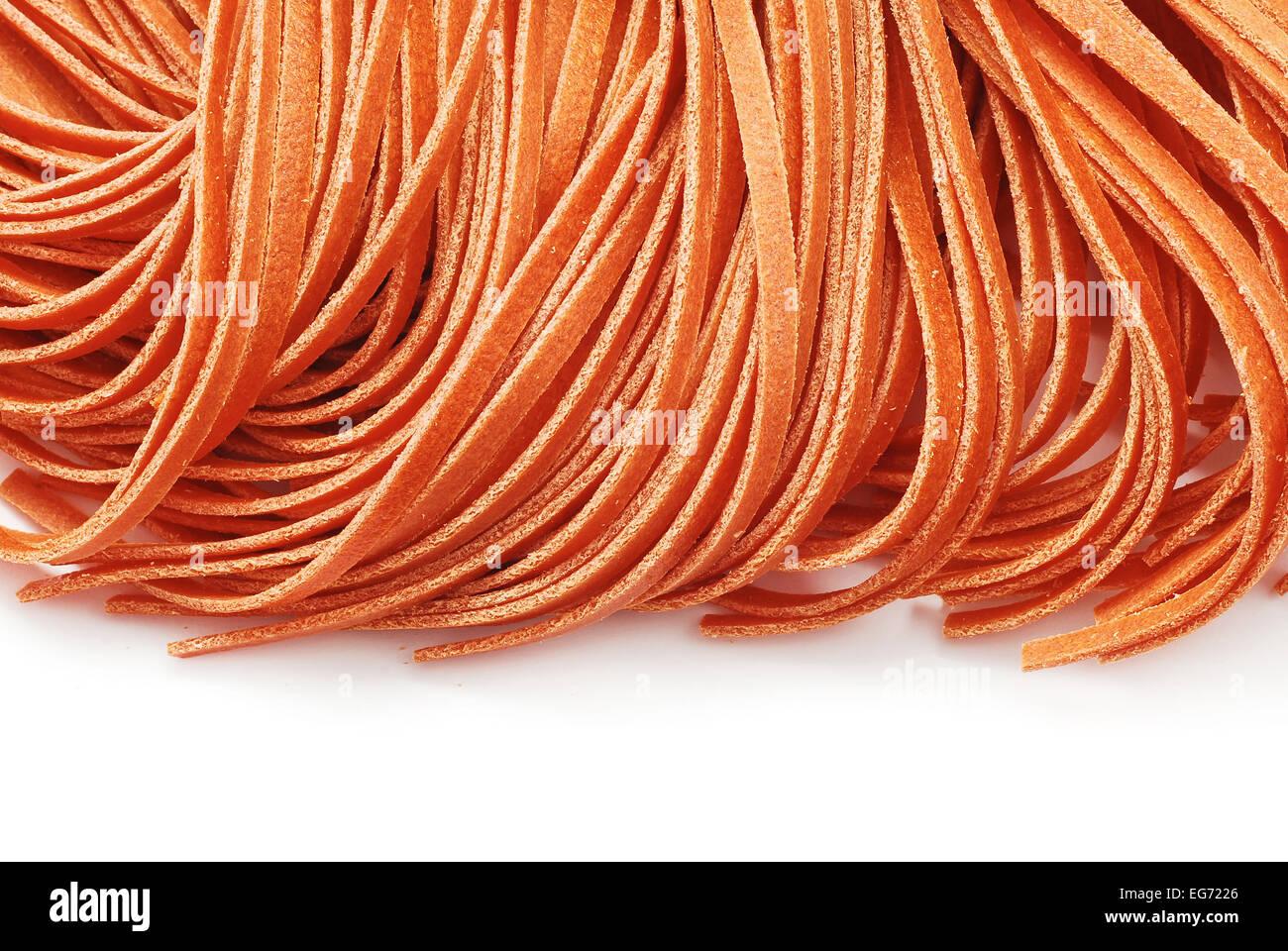 fettuccine red pasta on white - Stock Image