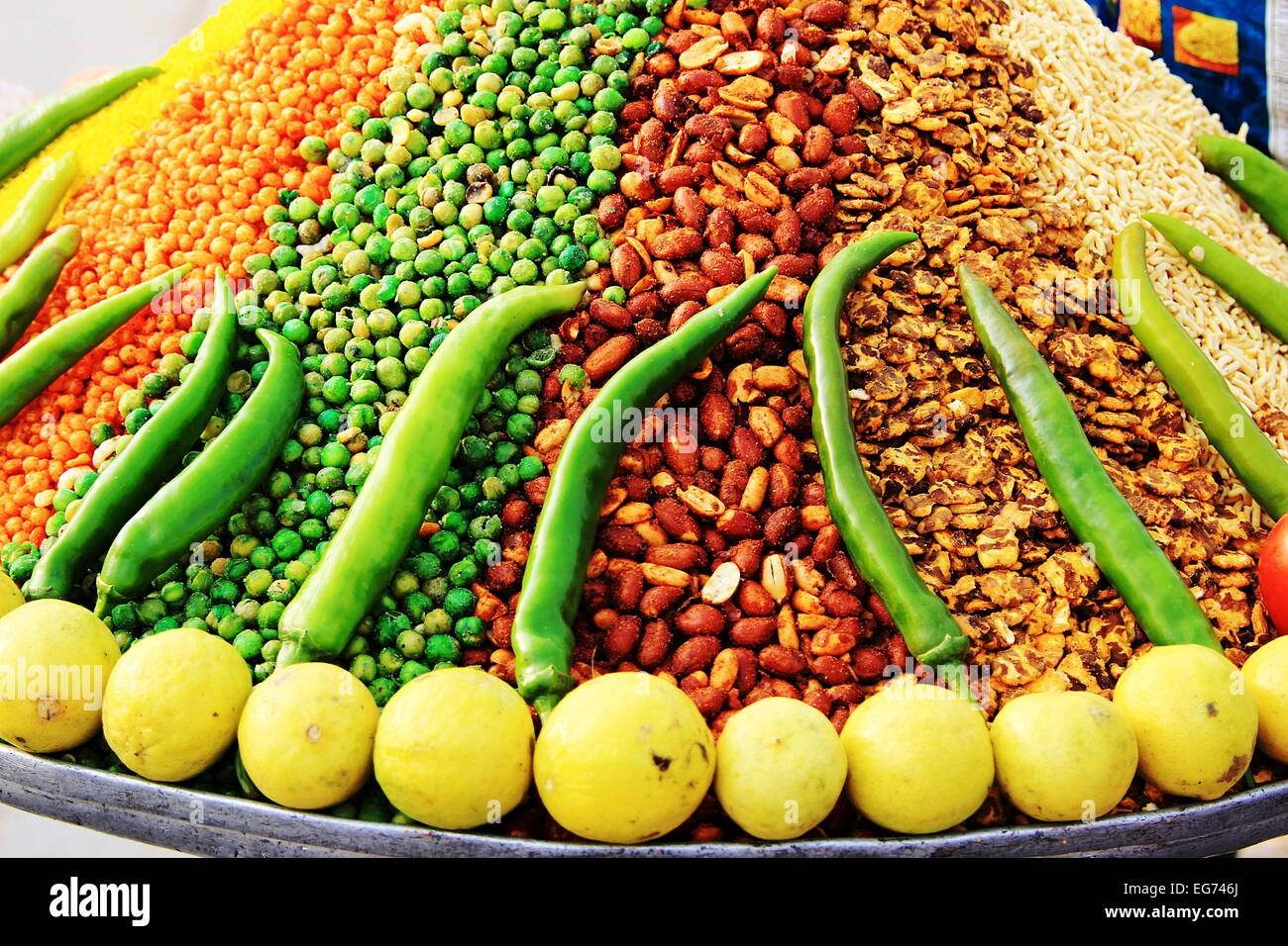 Tray of orange, green, red, yellow, white chats containing spiced peanuts, green peas, beans, etc. decorated with - Stock Image