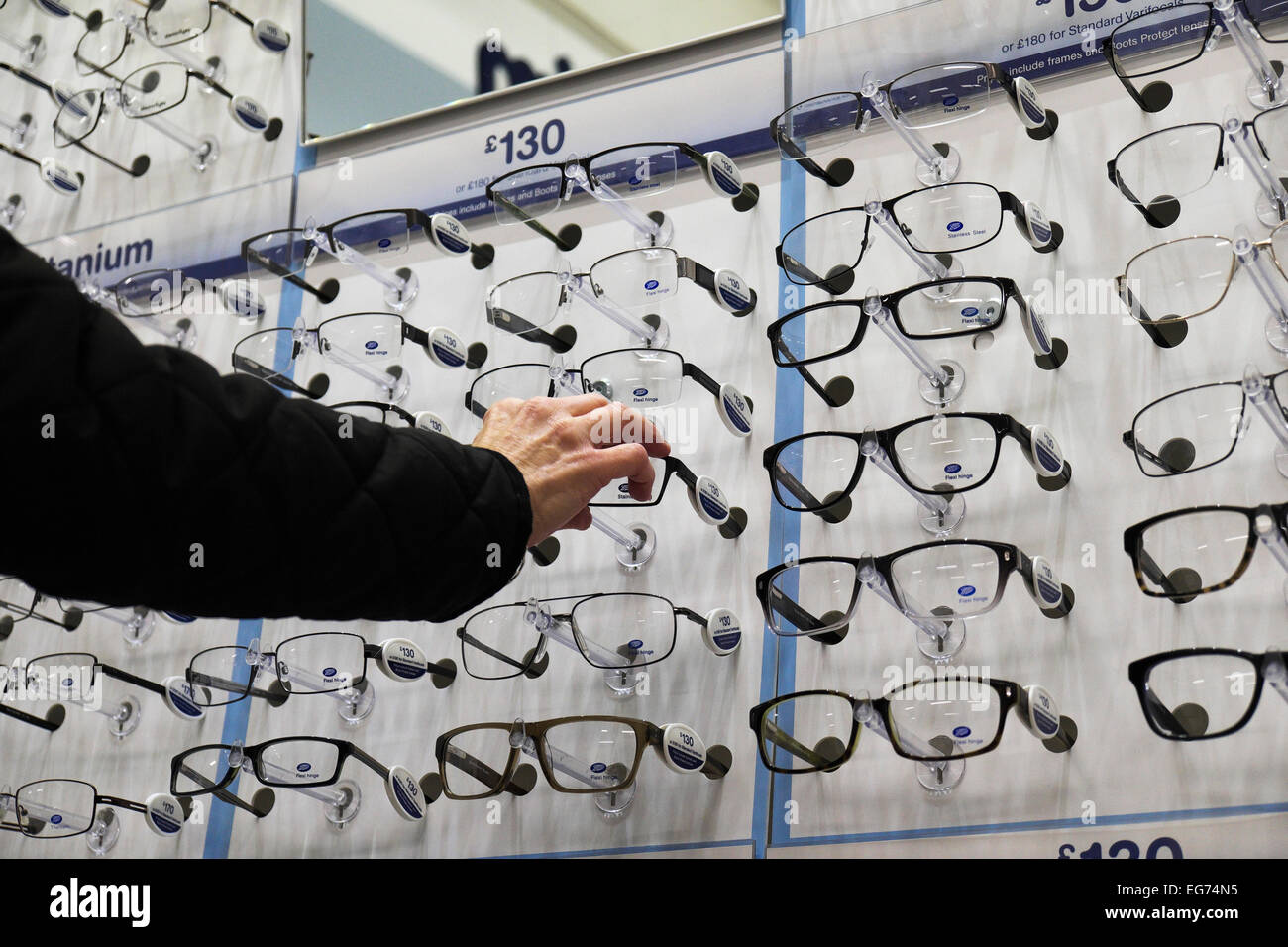 A customer choosing frames for new spectacles in a Boots opticians. - Stock Image