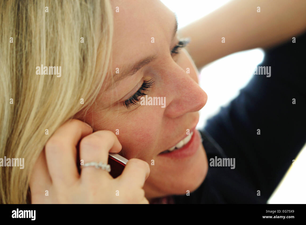 Blond lady talking on a cell phone - Stock Image