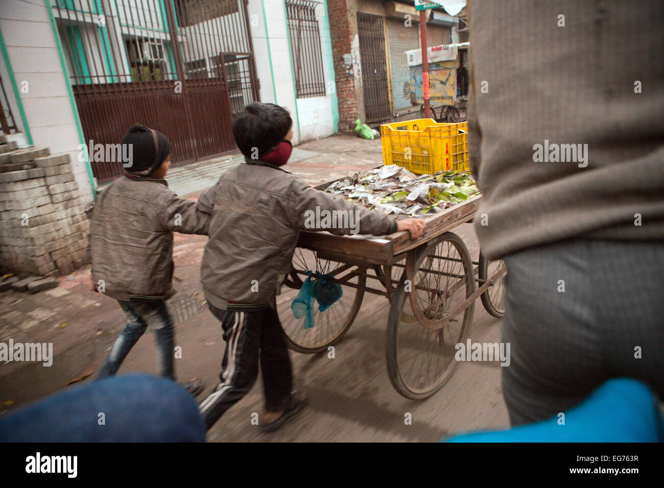 Children pushing a market cart in Lucknow, India. - Stock Image
