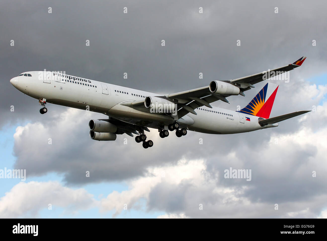 Philippine Airlines Airbus A340-300 approaches runway 27L at London Heathrow airport. - Stock Image