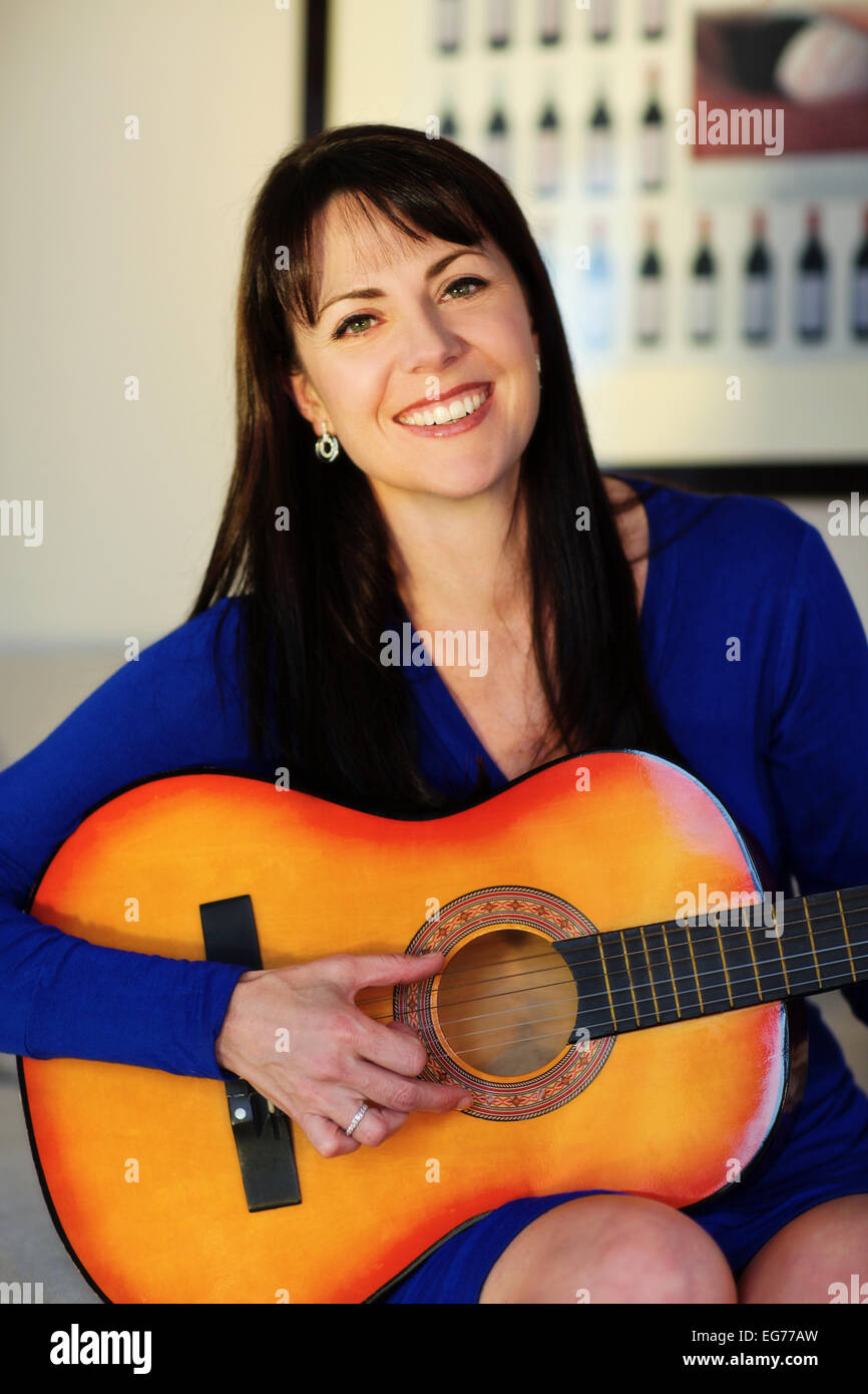 Portrait of very beautiful woman playing guitar - Stock Image