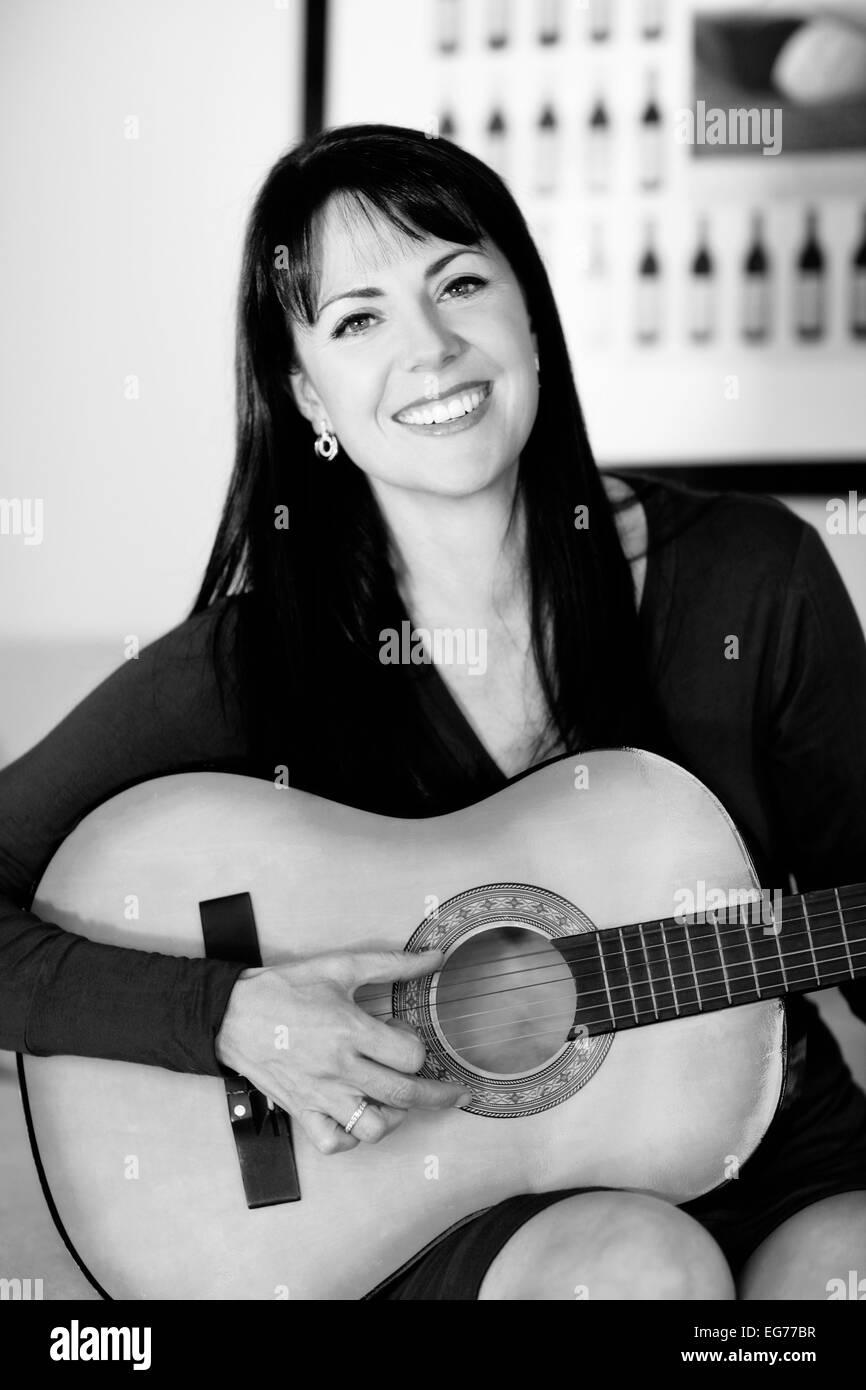 Monochrome portrait of very beautiful woman playing guitar - Stock Image