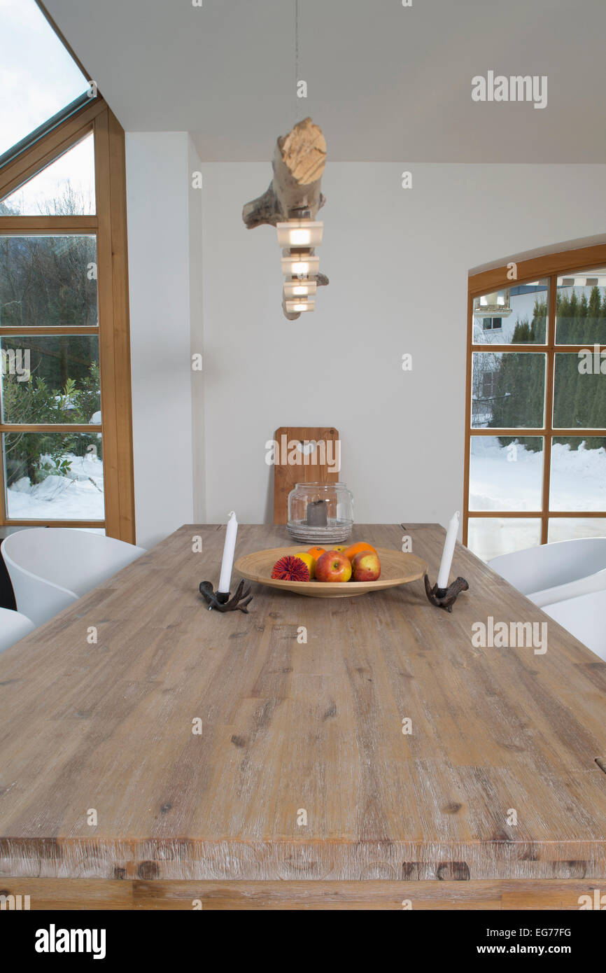 Fruit bowl and candle holders on wooden table - Stock Image