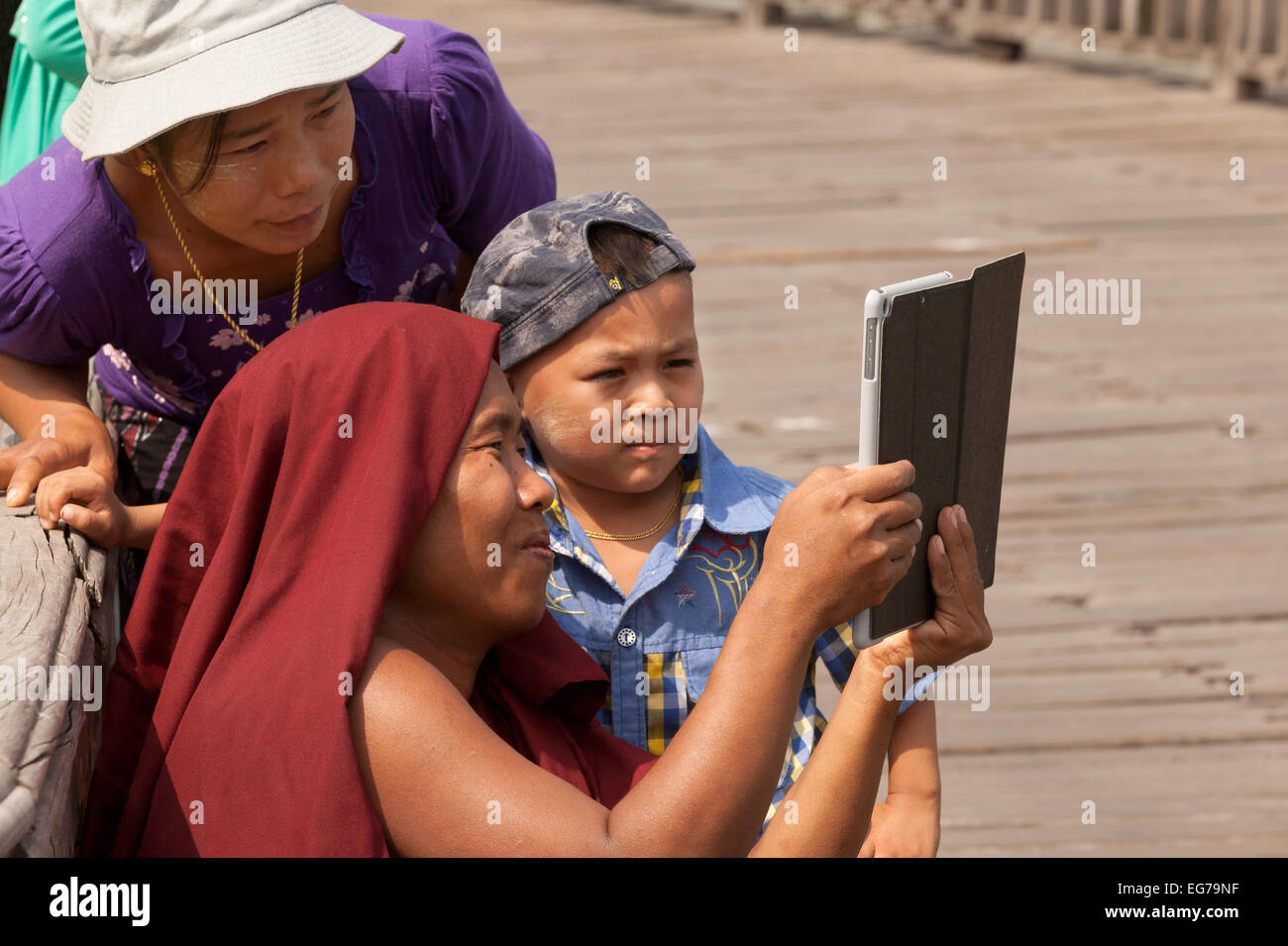 Burmese buddhist monk showing photos to a child on his tablet computer, Yangon, ( Rangoon ), Myanmar ( Burma ), - Stock Image
