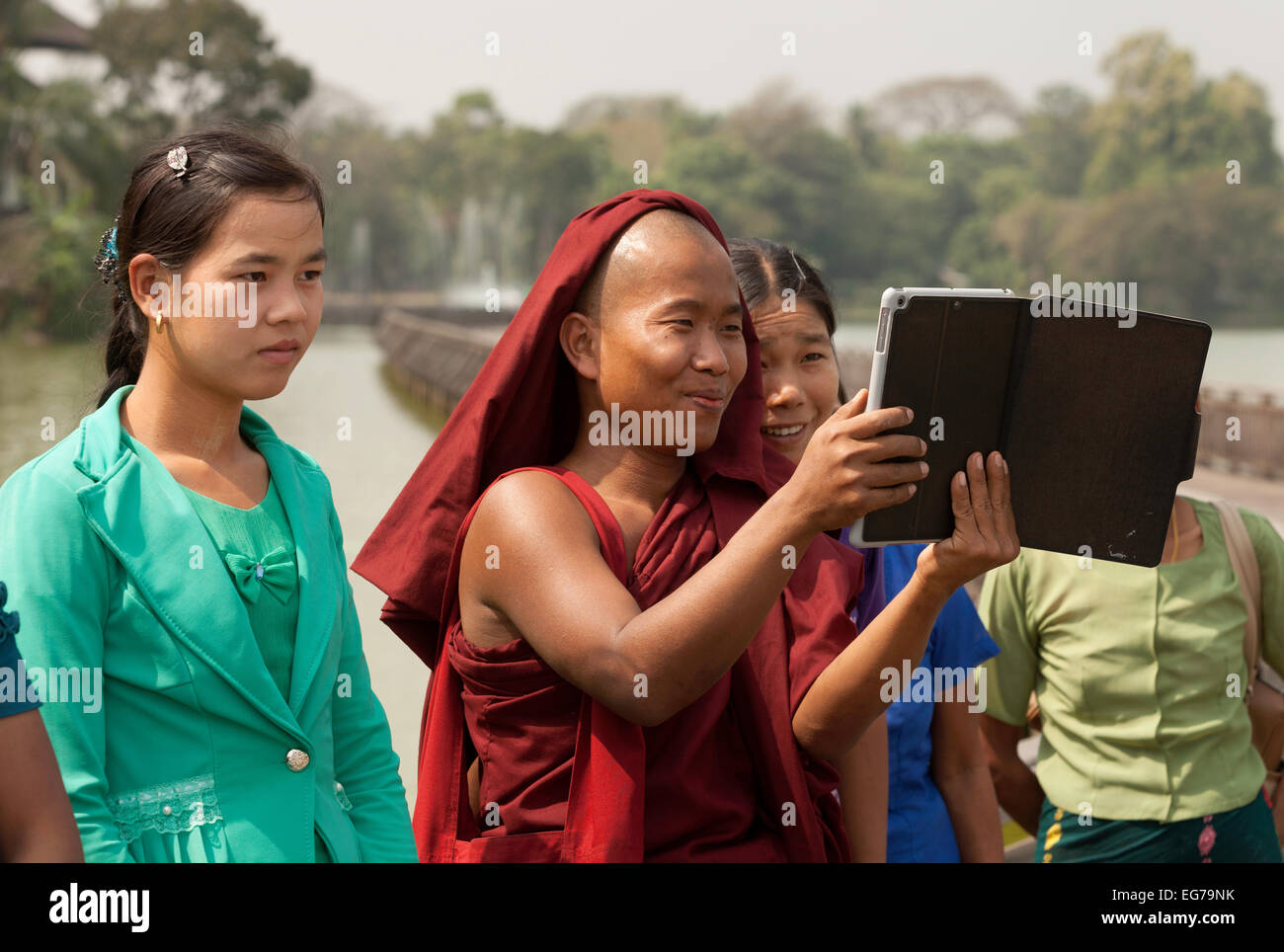A buddhist monk showing people photos on his tablet computer, Yangon, Myanmar ( Burma ), Asia - Stock Image
