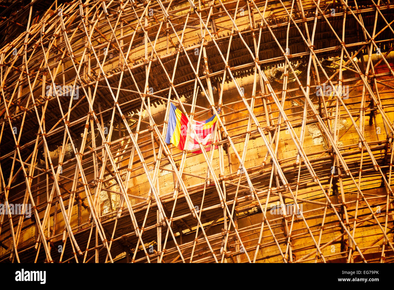 The buddhist flag flying in the bamboo scaffolding on the Shwedagon Pagoda during re-laying of the gold leaf, Yangon, - Stock Image