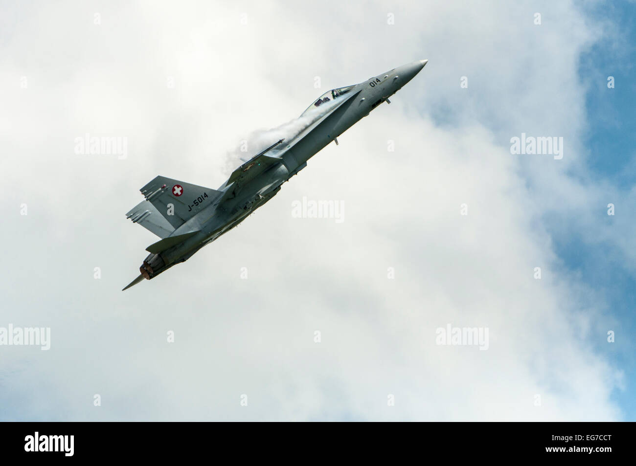 Swiss airforce F/A - 18C Hornet in cloudy sky with smoke generators - Stock Image