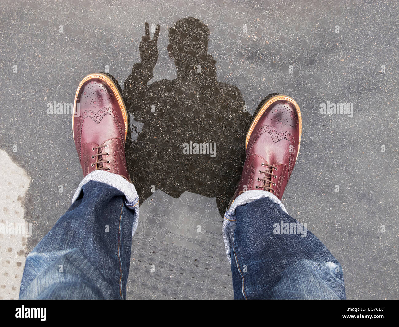 a selfie reflection photograph in a puddle making a two finger peace sign - Stock Image