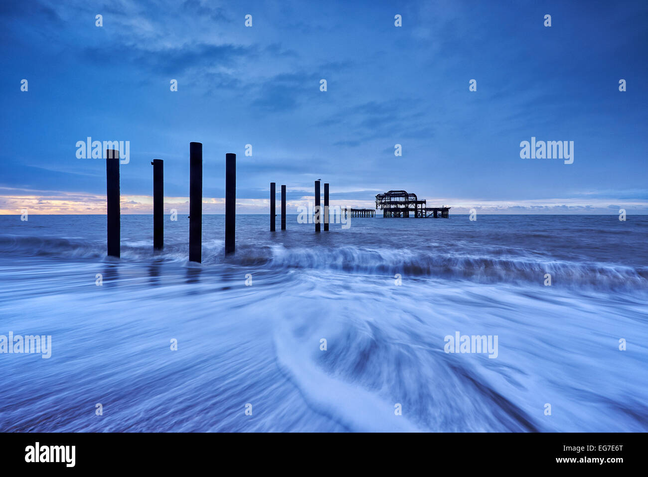 The decaying remains of Brighton's West Pier at sunrise with the tide coming in. - Stock Image