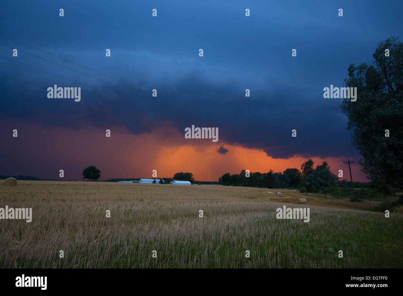 An evening thunderstorm squall line and shelf cloud are backlit by the setting evening sun producing vibrant orange - Stock Image