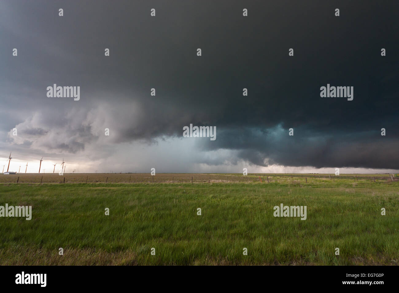 A powerful tornado warned supercell thunderstorm rolls across the Texas landscape with a large wall cloud and green - Stock Image