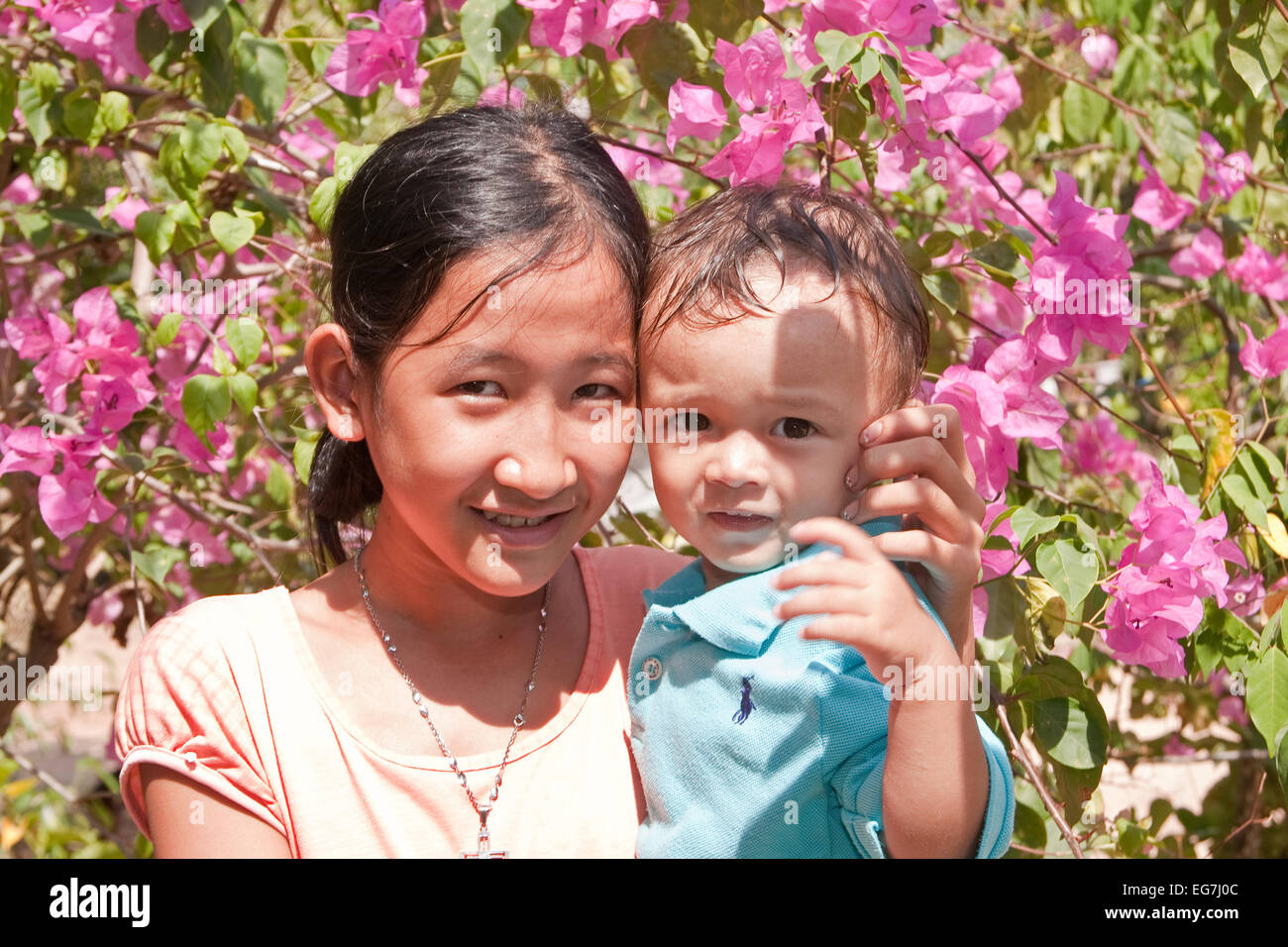 Young girl with small child on the arm, Phu Quoc, Vietnam, Asia Stock Photo