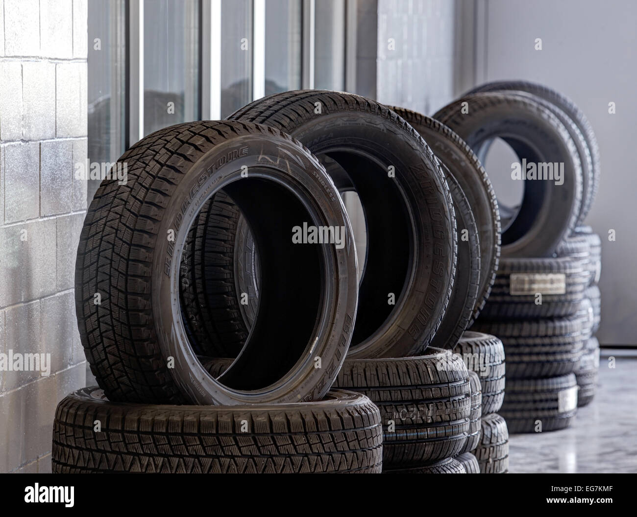 Stacks of tires, with tread patterns for various driving conditions, for sale in an automotive repair garage. - Stock Image