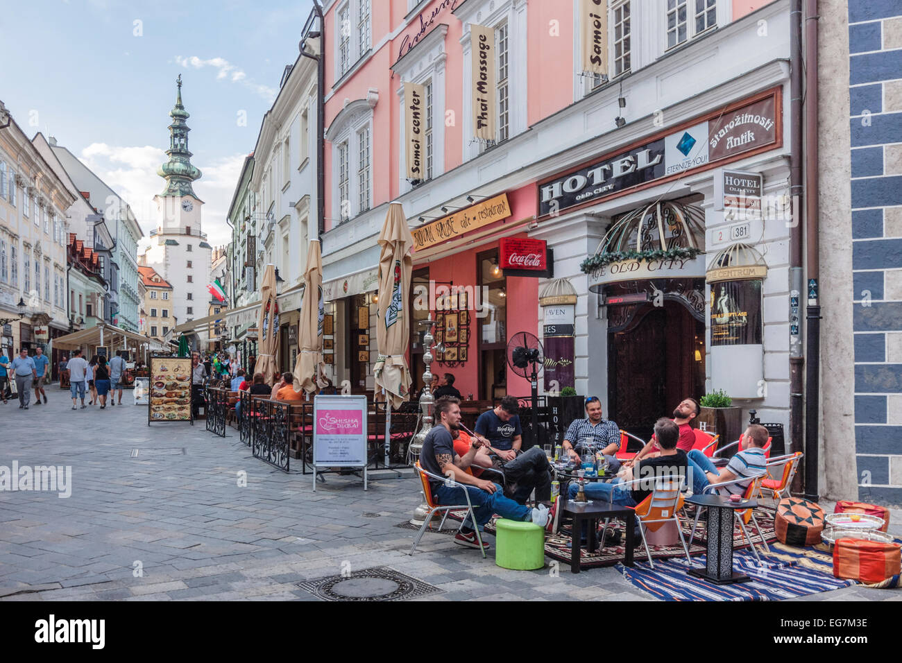 Tourists at a terrace cafe in Venturska Michalska the Old Town´s main street with Michael's Gate in background. - Stock Image