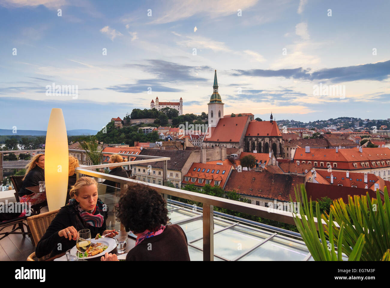 Women at panoramic terrace of Sky restaurant overlooking old town, cathedral and castle in Bratislava, Slovakia - Stock Image