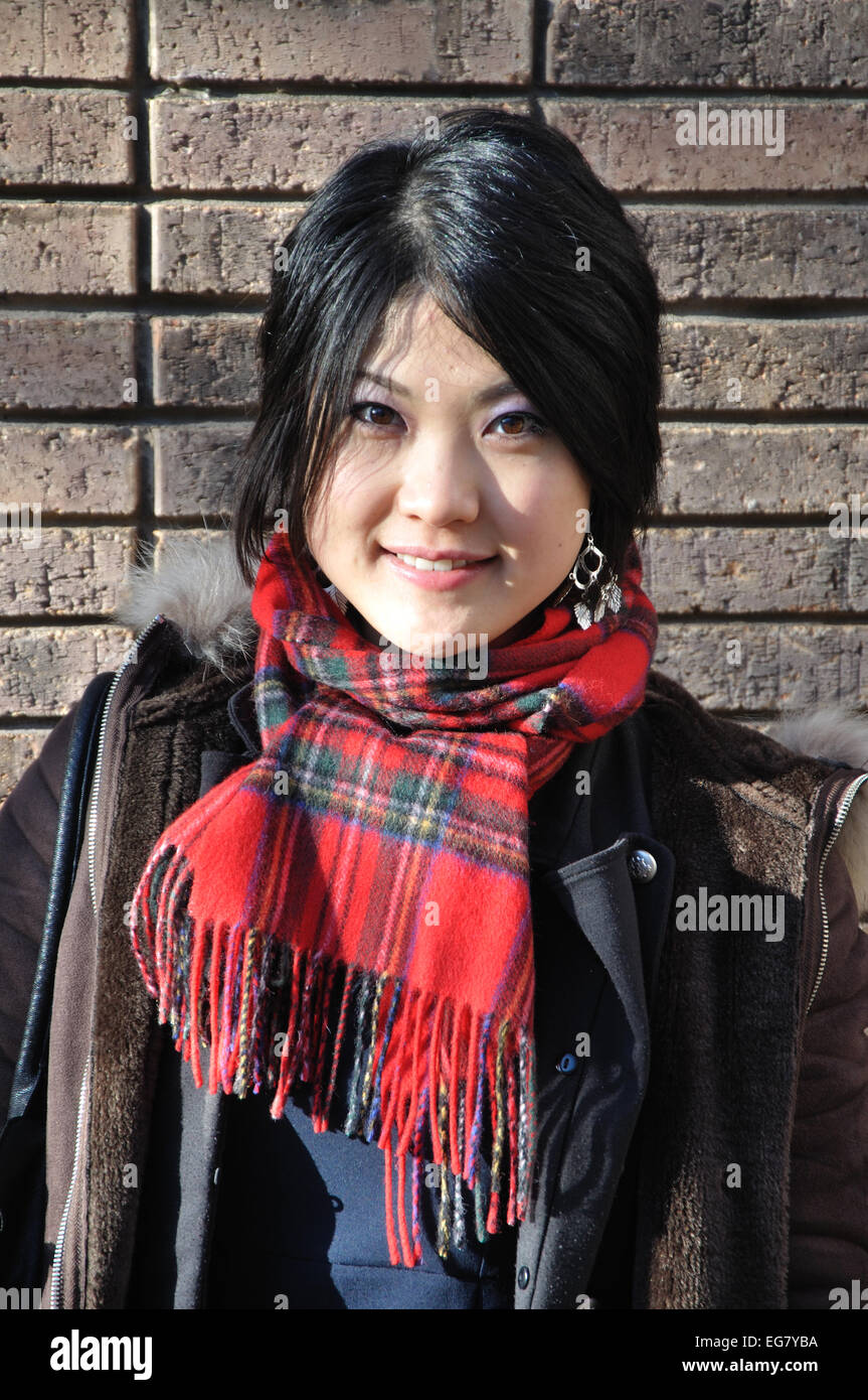 Japanese woman wearing tartan scarf, England, UK - Stock Image
