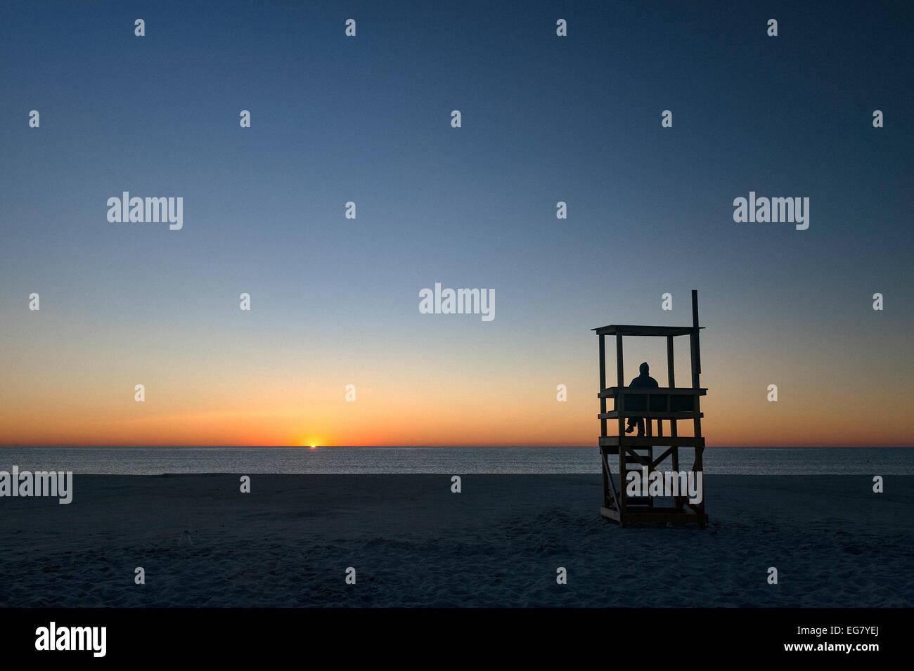 Person watches the sunrise over the ocean, Nauset Beach, Cape Cod National Seashore, Cape Cod, Massachusetts, USA - Stock Image