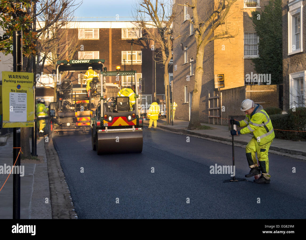 Laying a new road surface on a street in London UK - Stock Image