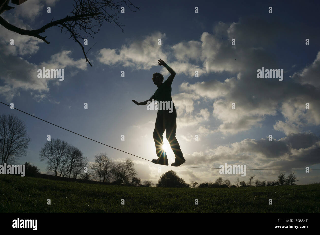 Man walking and balancing on a slackline backlit by the sun. England UK - Stock Image
