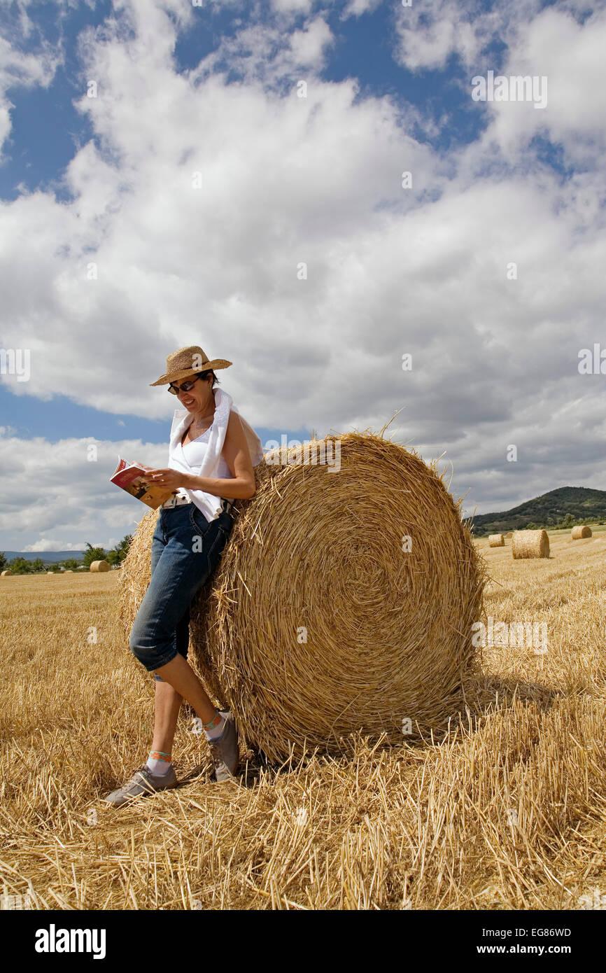 Woman reading on a roll of straw packed in a freshly cut wheat field Villarcayo Burgos Castilla Leon Spain mujer - Stock Image