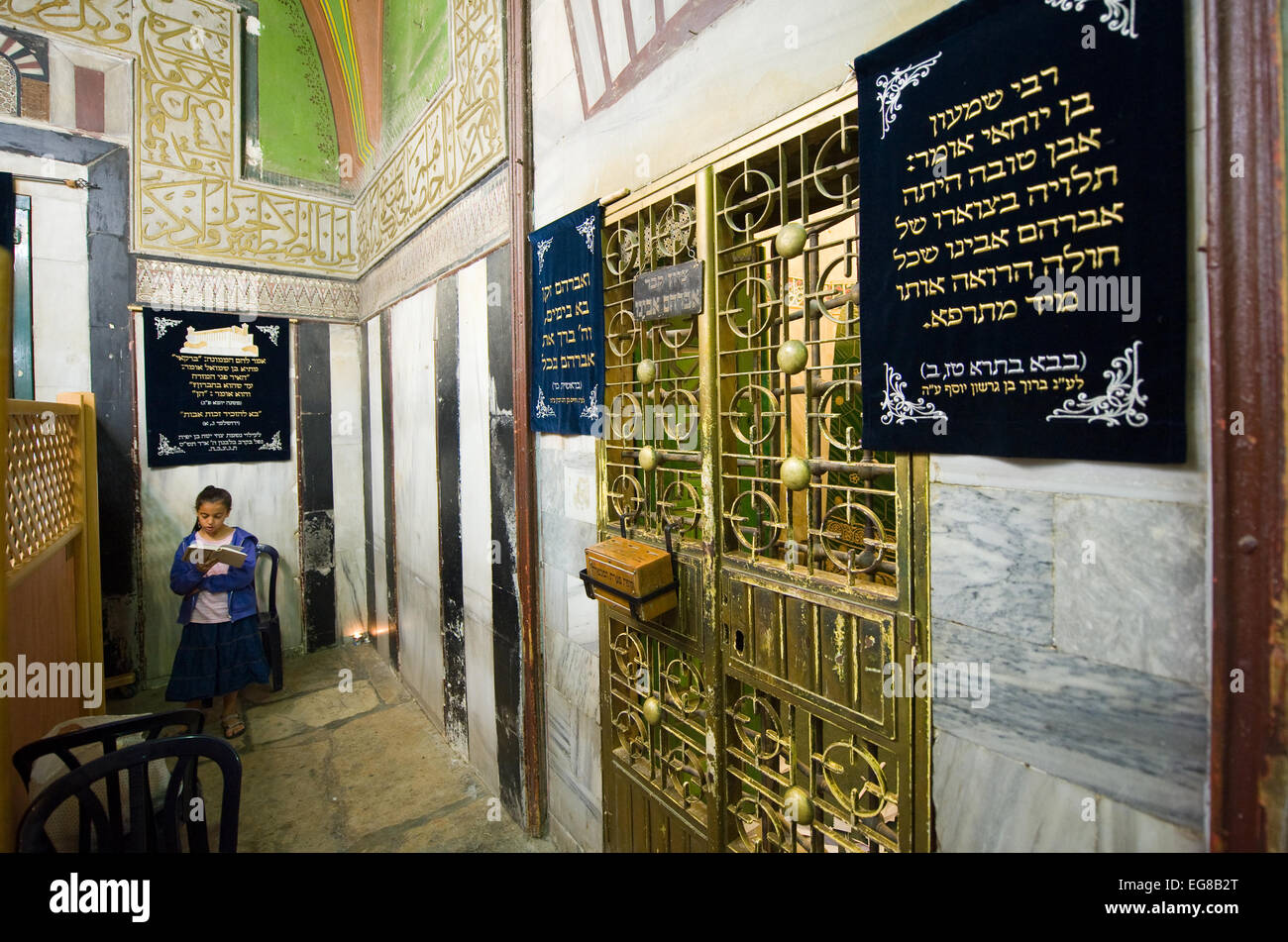 A young girl is reading the torah close to the tomb of patriarch Abraham behind the green iron door - Stock Image