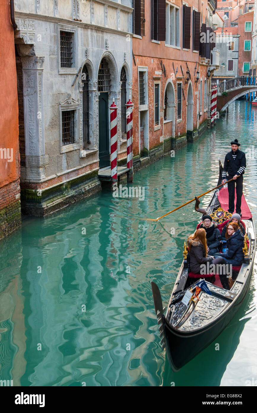 Gondola with gondolier and tourists in a narrow water canal, Venice, Veneto, Italy - Stock Image