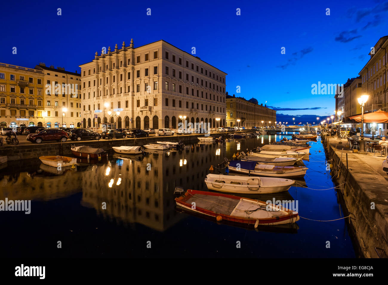 Trieste, Italy - A view of the Gran Canale with boats moored in the water at sunset - Stock Image
