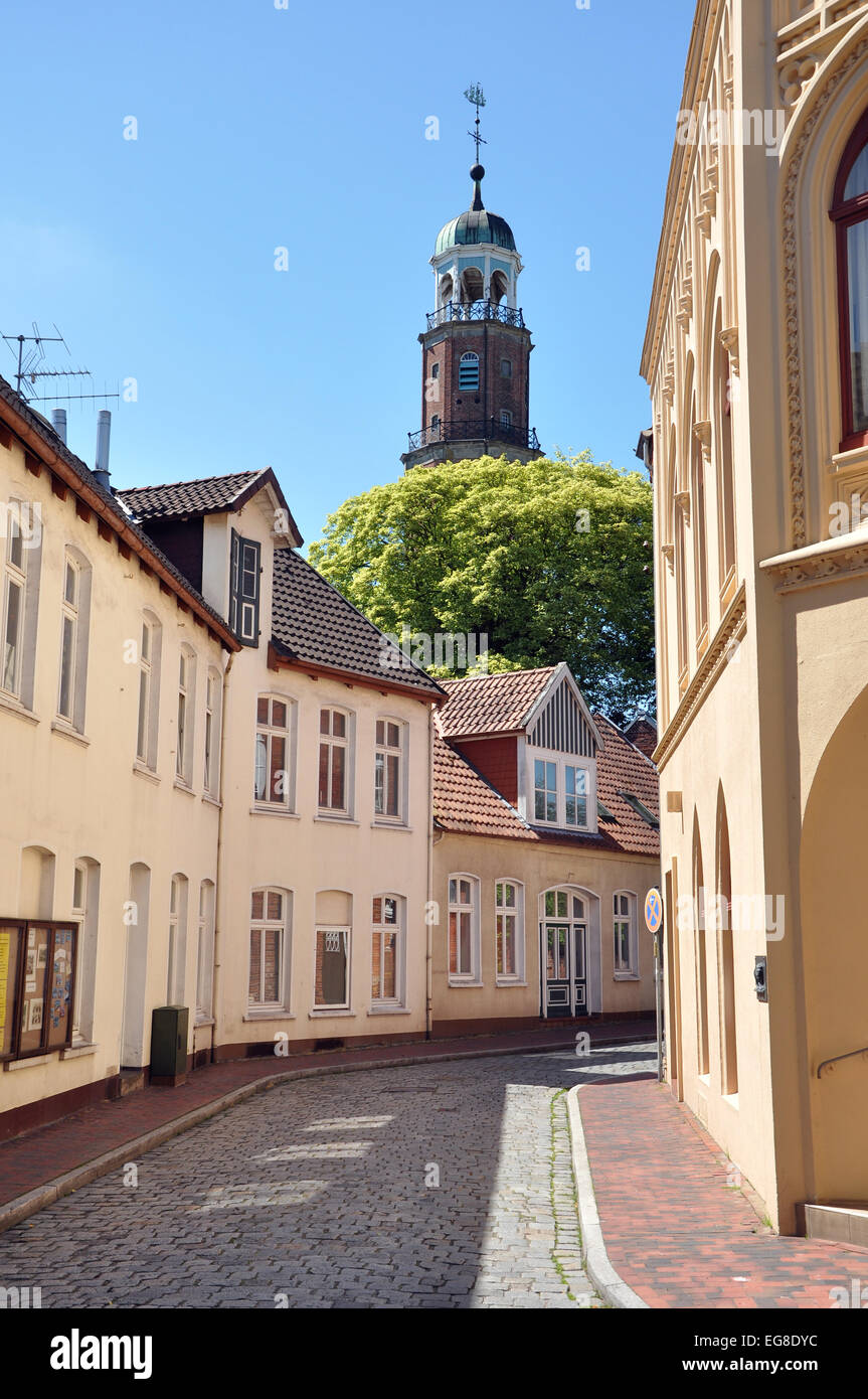Street view at houses and a church tower of Leer, Germany - Stock Image