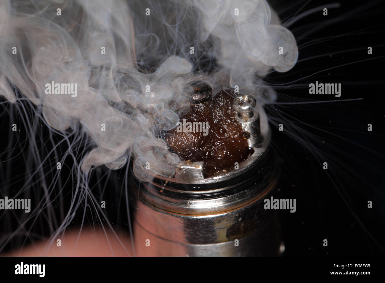 Vapor rises off of the heating element of an e-cigarette. - Stock Image