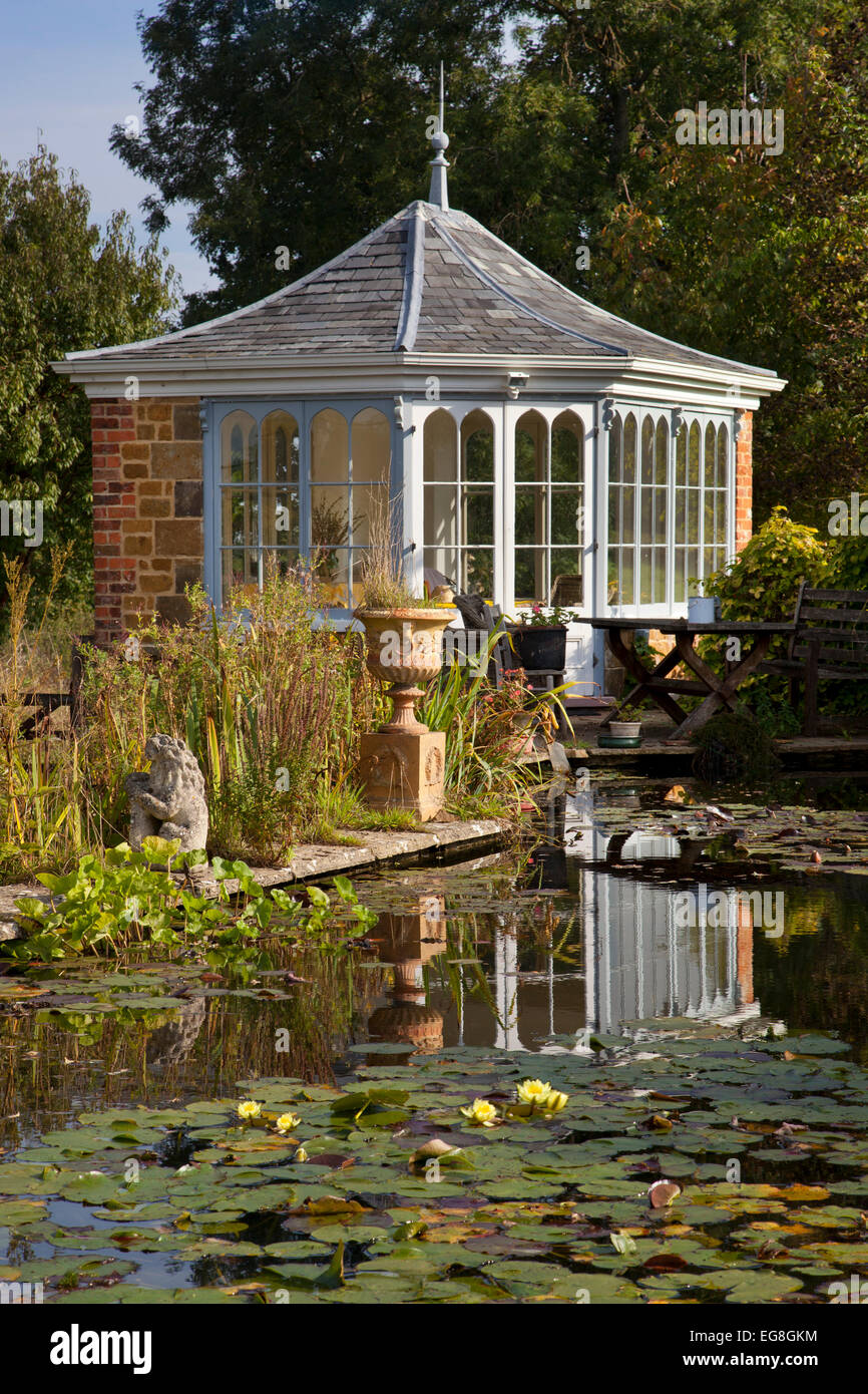 Large garden pond in summer with brick summerhouse and seating overlooking water and lillypads,Garden,Oxfordshire,England - Stock Image