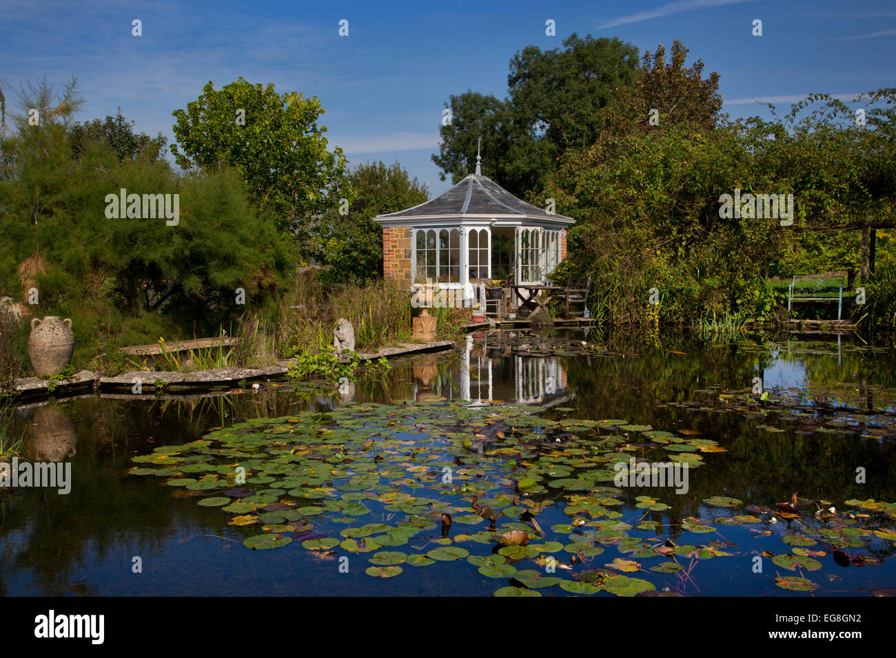 Large garden pond in summer with brick summerhouse and seating overlooking water and water lilles,Garden,Oxfordshire,England - Stock Image
