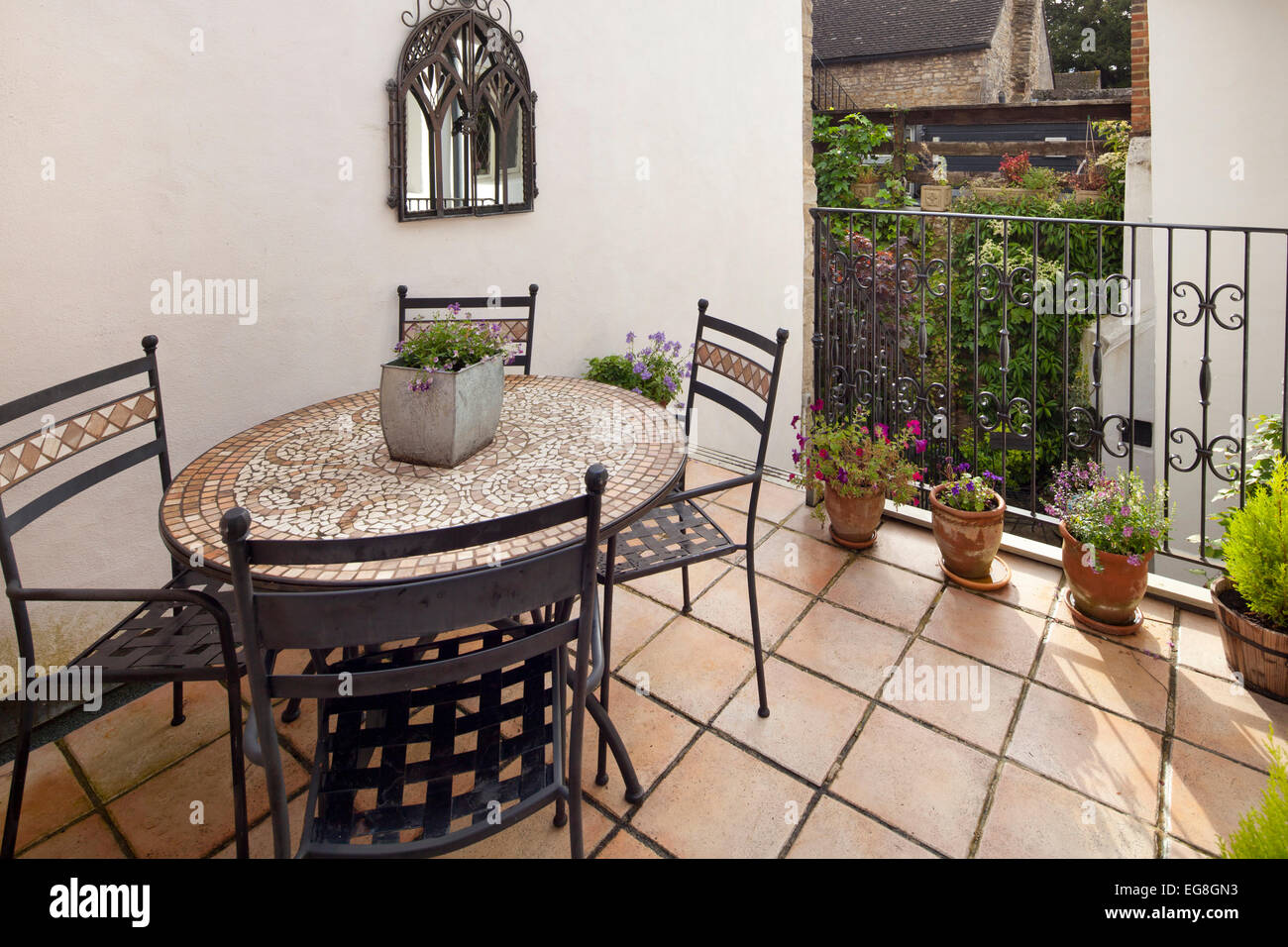 Small balcony with terracotta tiled floor,pots and outdoor metal seating, Garden,Oxfordshire,England - Stock Image