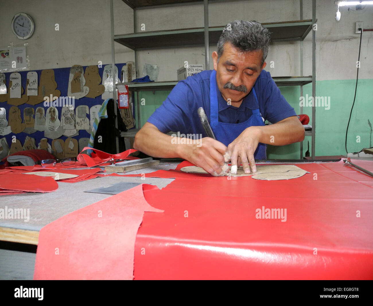 A staff member of manufacturer of boxing gloves Cleto Reyes works on the production of a professional boxing glove - Stock Image