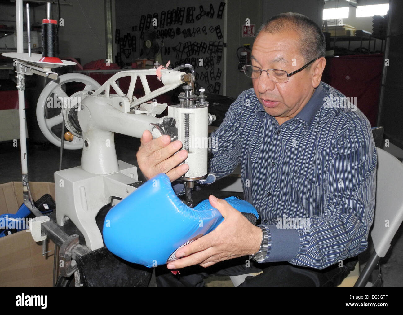 The head of manufacturer of boxing gloves Cleto Reyes, Alberto Reyes, works on the production of a professional - Stock Image