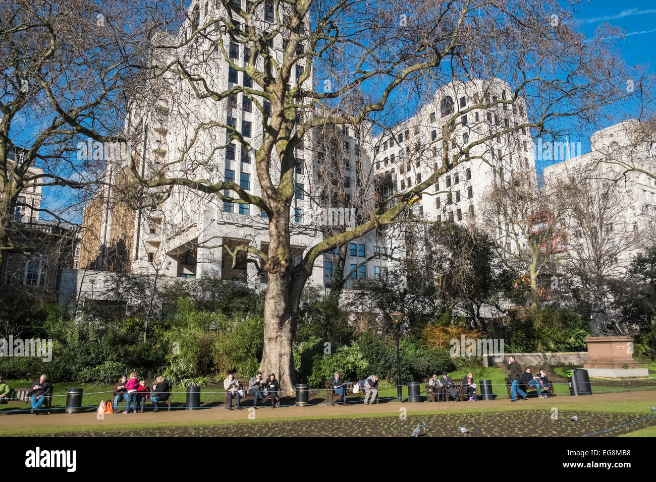 People sitting and relaxing in winter sunshine, Victoria Embankment Gardens, London, UK - Stock Image