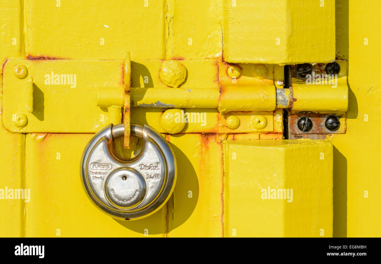 Padlock on the latch to a wooden shed door. - Stock Image