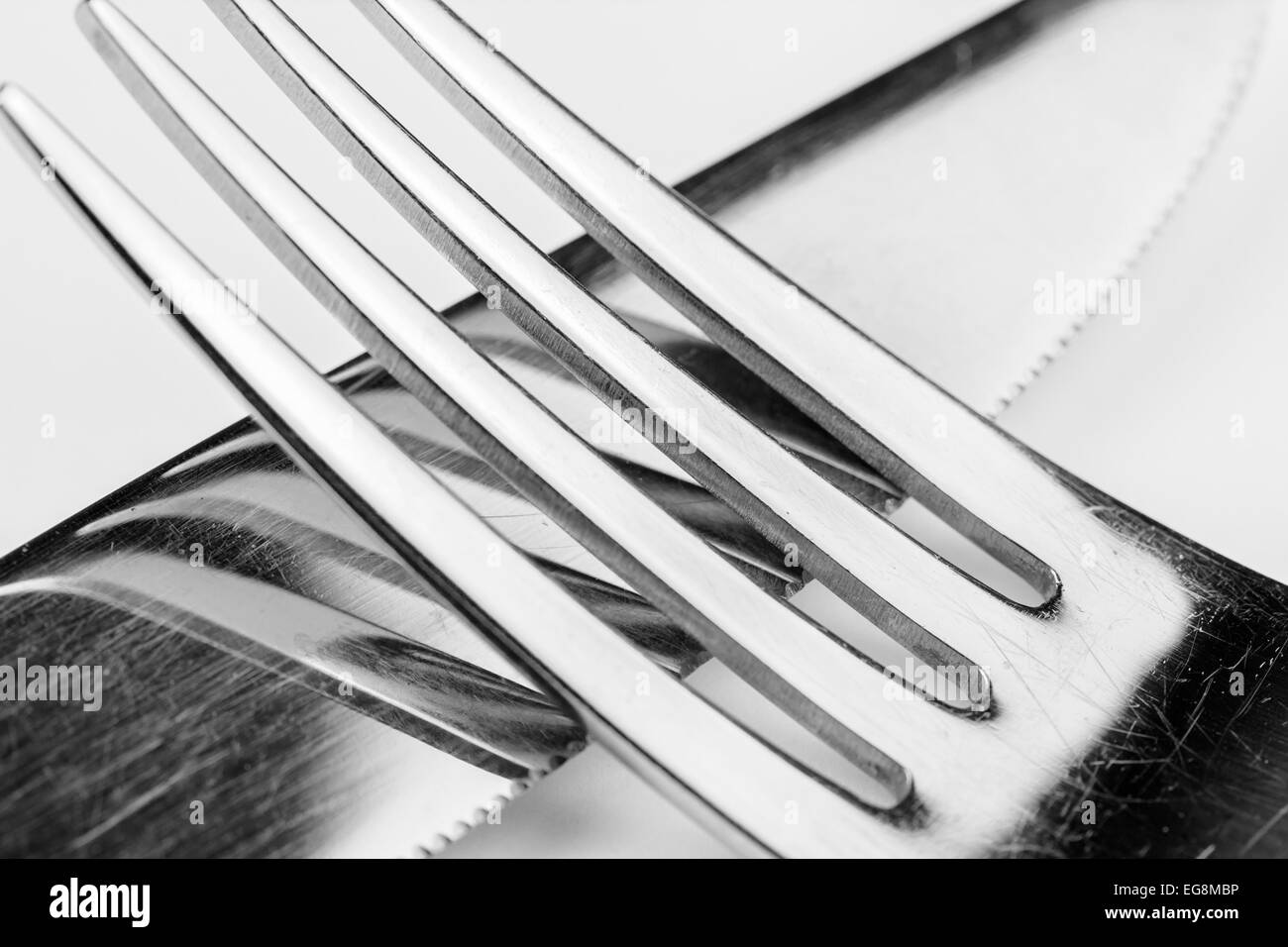 Stainless steel knife and fork with a reflection of the fork. - Stock Image