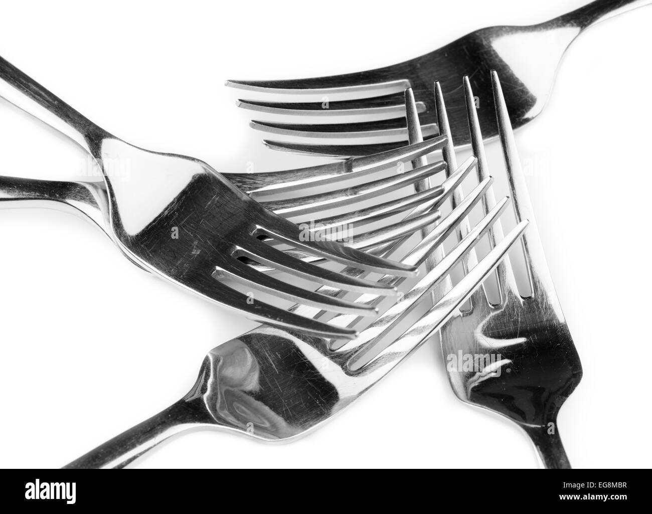 Several stainless steel forks on a white background. - Stock Image