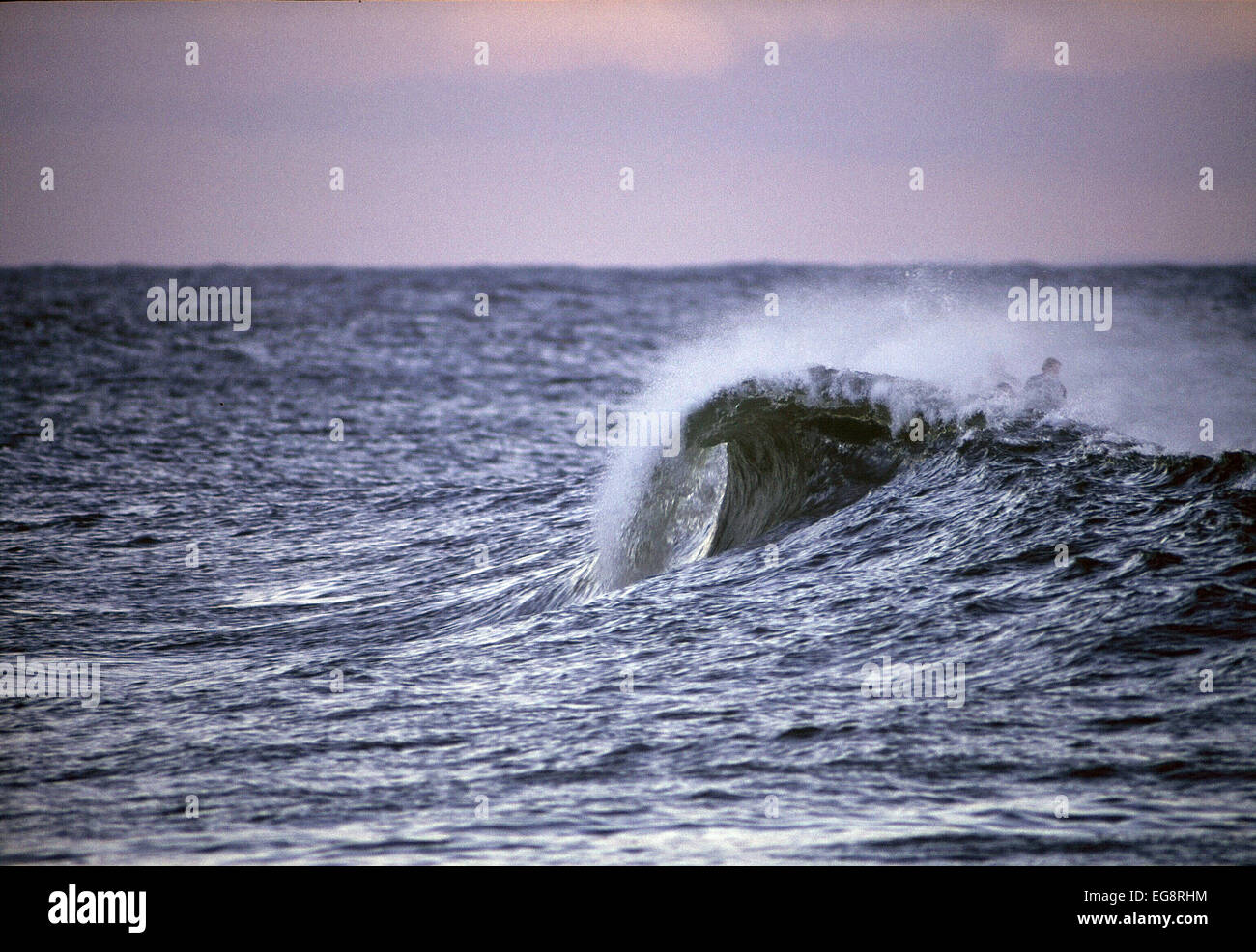 Surfer makes it over the top of  a tubing wave on Gower in Wales.  Wedge shaped wave. - Stock Image