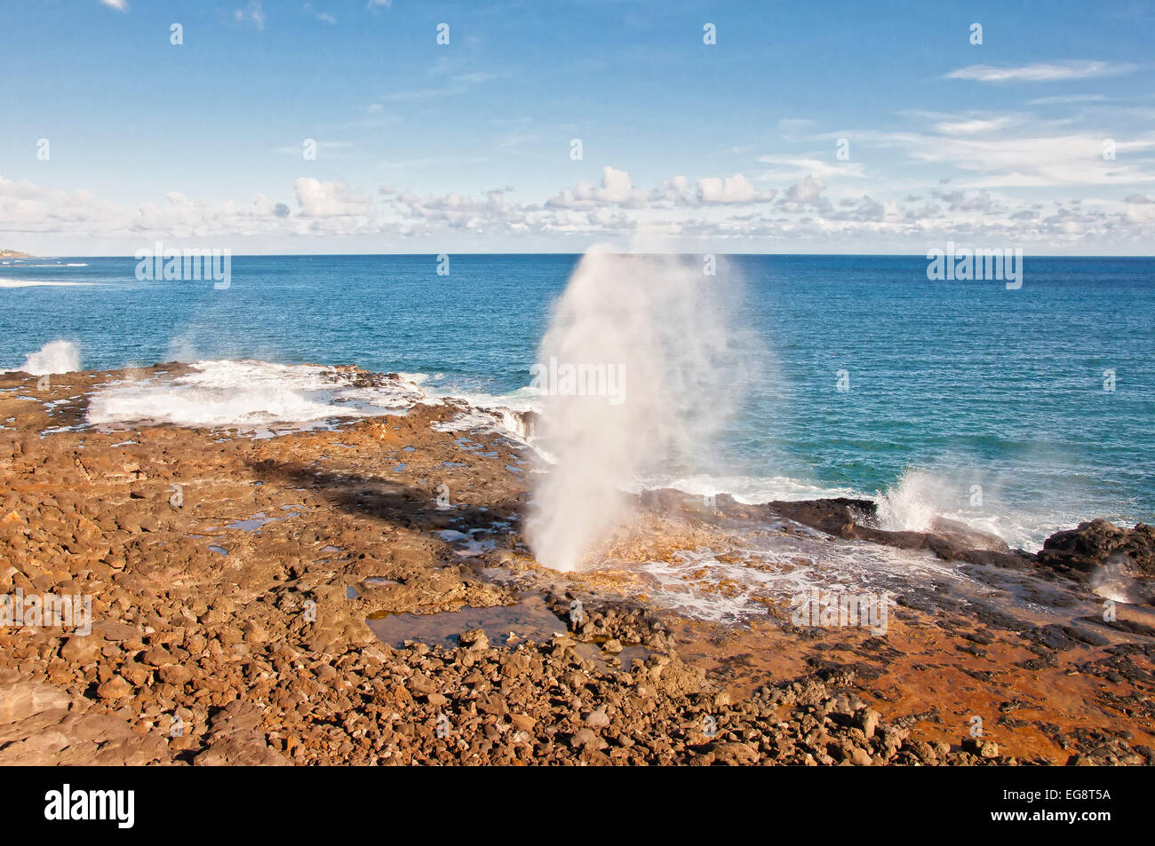 Rush of ocean water being spewed out of Spouting Horn, a natural blow hole created by a  lava tube on the island - Stock Image