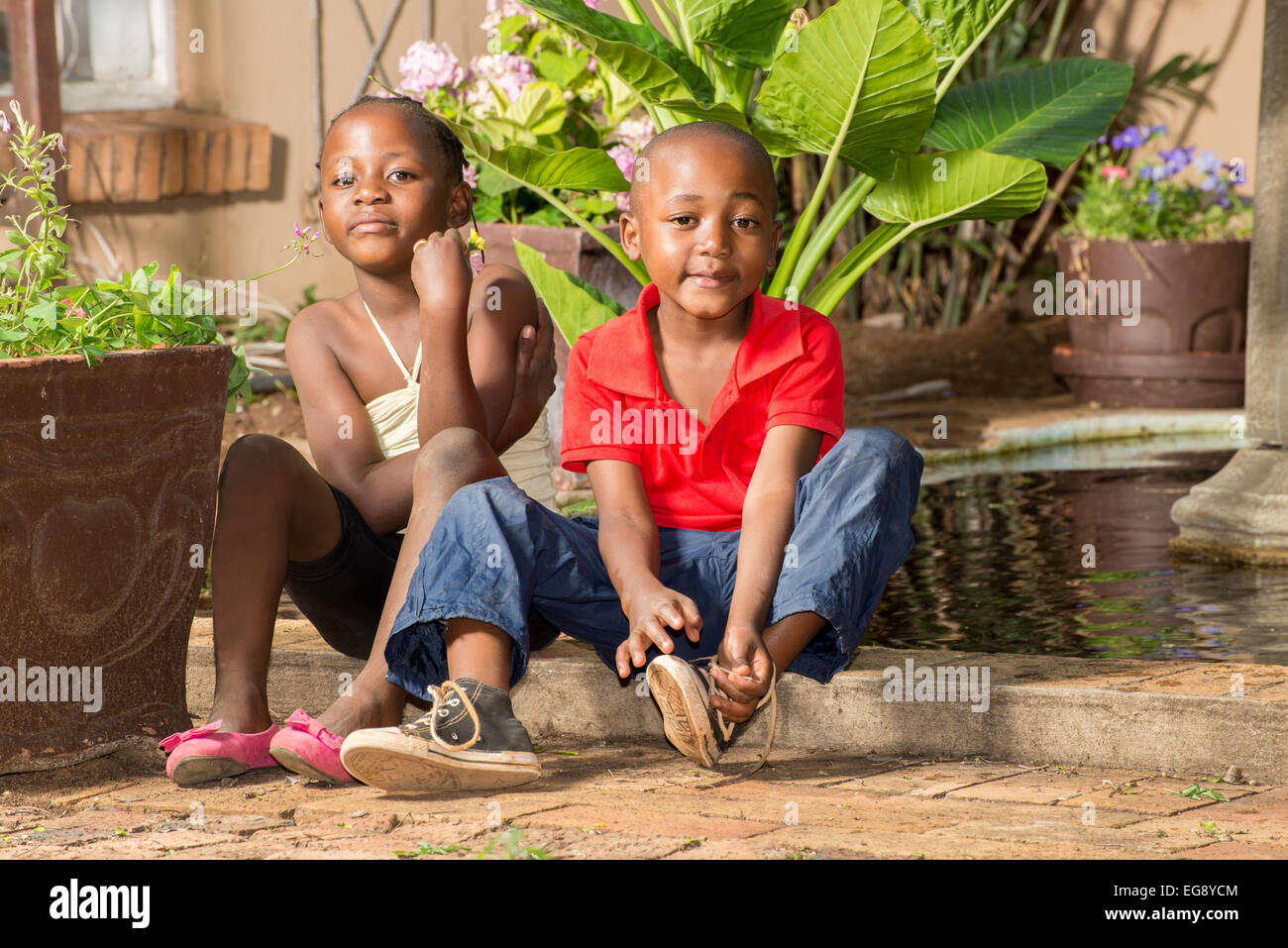 Boy ties his shoe laces after he and his twin sister played at the pond by their house. - Stock Image