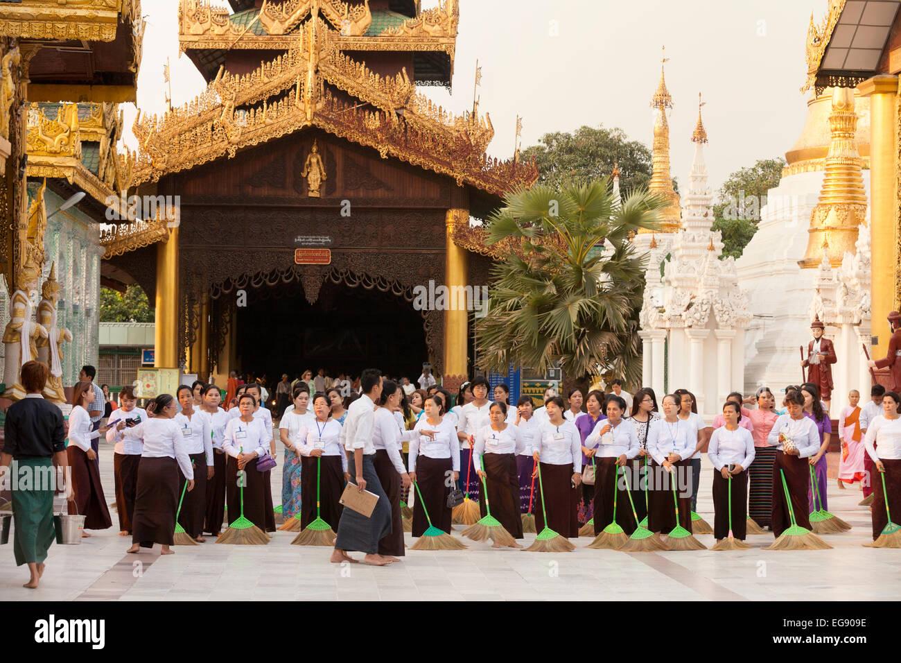 Young women sweeping the ground at sunset, the Shwedagon Pagoda, Yangon, Myanmar ( Burma ), Asia - Stock Image