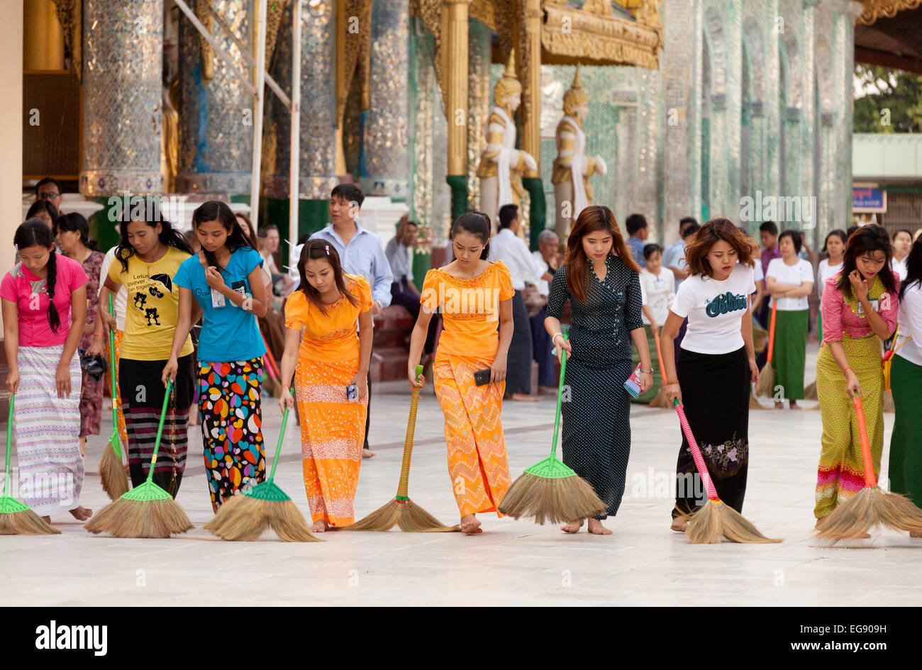 Young Burmese women sweeping the floor at sunset, Shwedagon Pagoda, Yangon, Myanmar ( Burma ), Asia Stock Photo