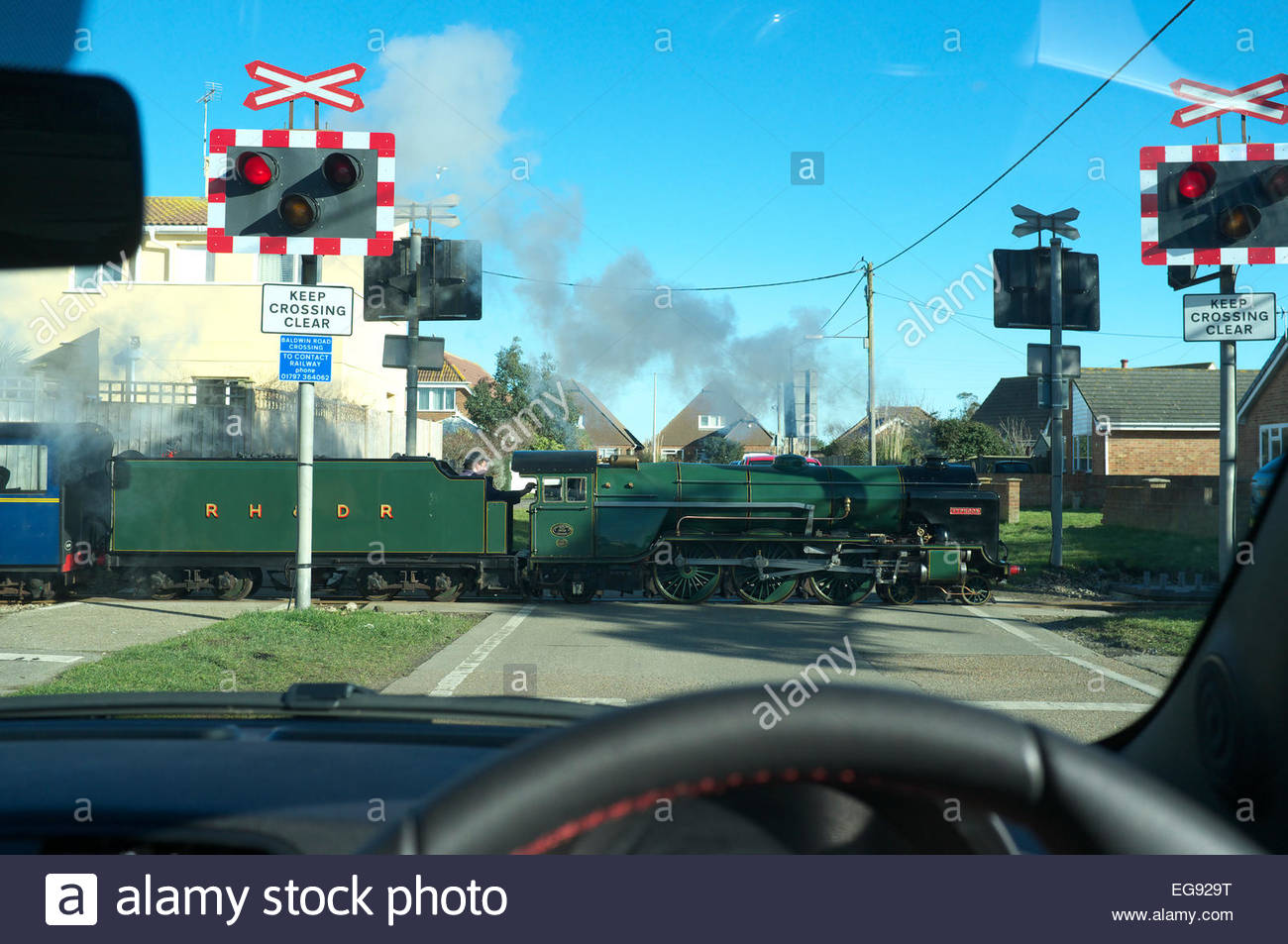 View from a car of narrow gauge steam loco Typhoon of the RH&DR passing over a level crossing in Greatstone-on-Sea, Stock Photo