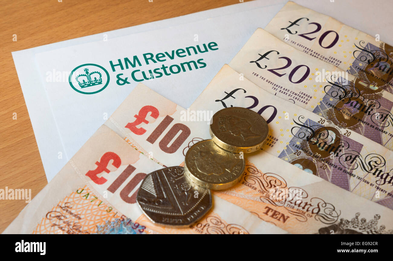 HMRC (Her Majesty's Revenue And Customs) letterhead on a desk surrounded by money - pounds Sterling. Stock Photo